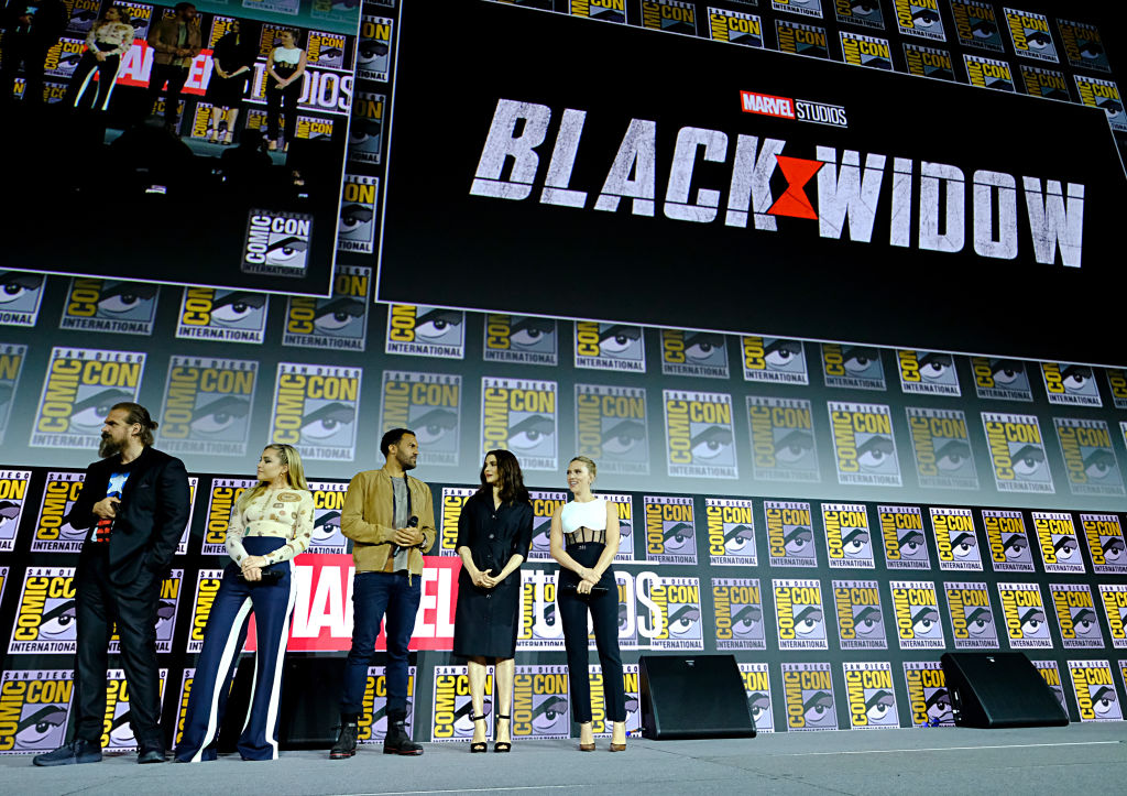 Cast of 'Black Widow' on stage with repeating background