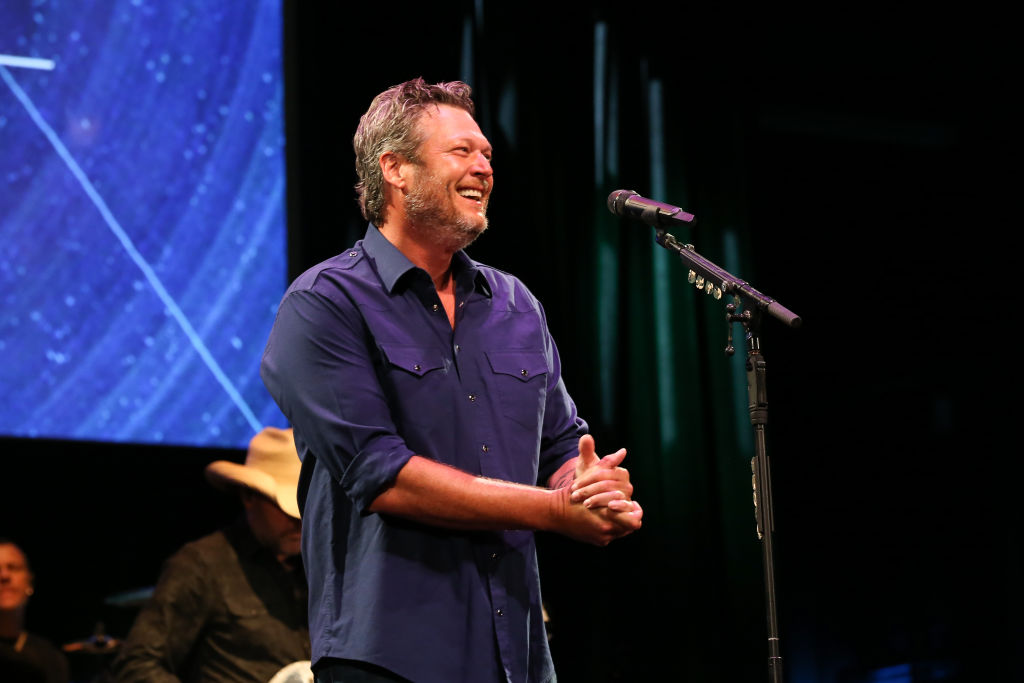 Blake Shelton in front of a microphone, smiling