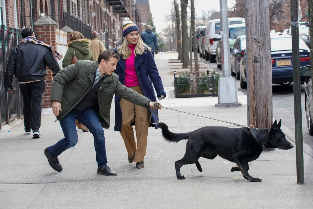 Jamie Reagan (Will Estes) and Eddie Janko (Vanessa Ray) walking a black dog