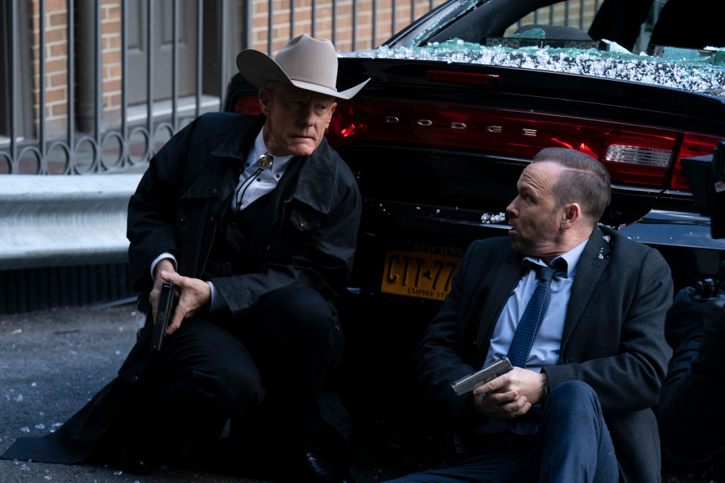 Lyle Lovett and Donnie Wahlberg on set of Blue Bloods, crouched behind a car holding prop guns