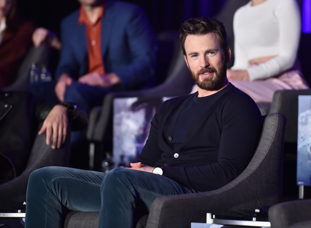 Chris Evans sitting in a chair and smiling