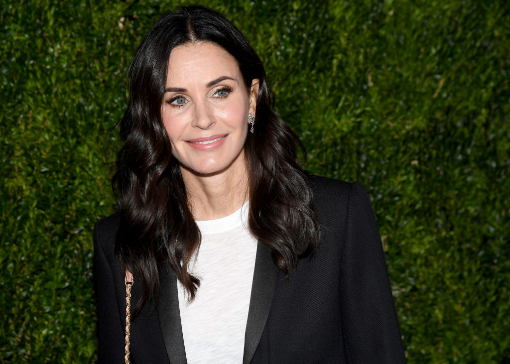 Courteney Cox smiling, looking off camera, in front of bushes
