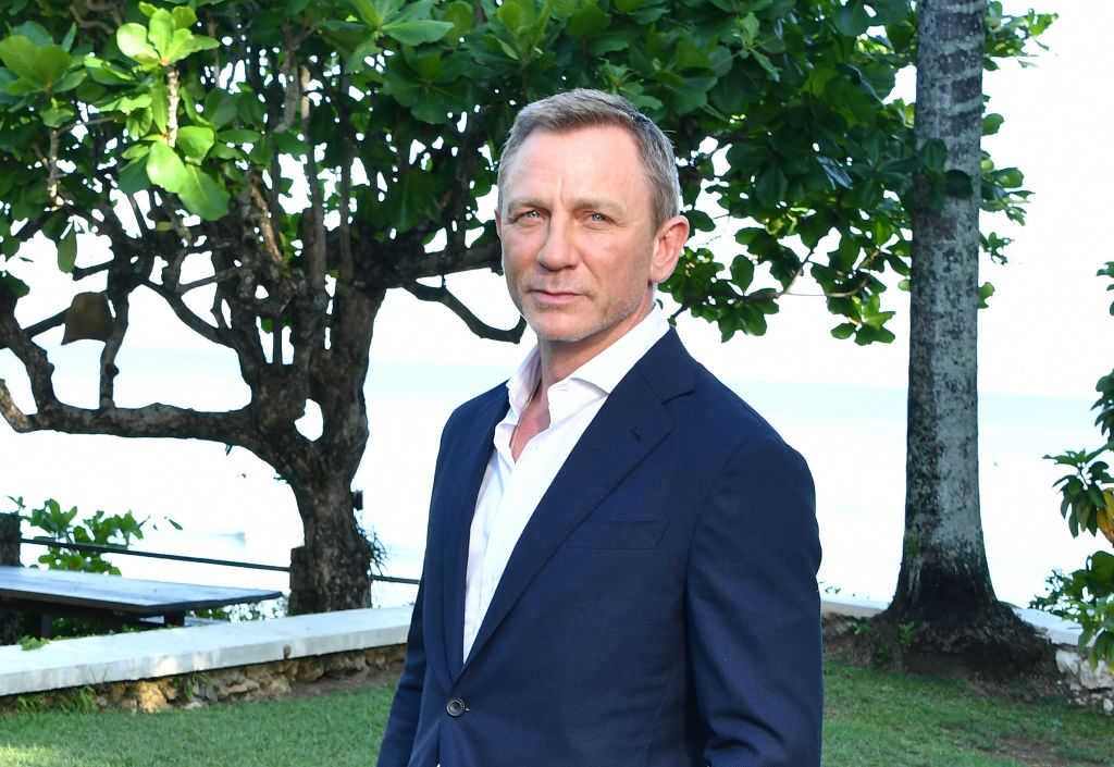 Daniel Craig smiling in front of trees