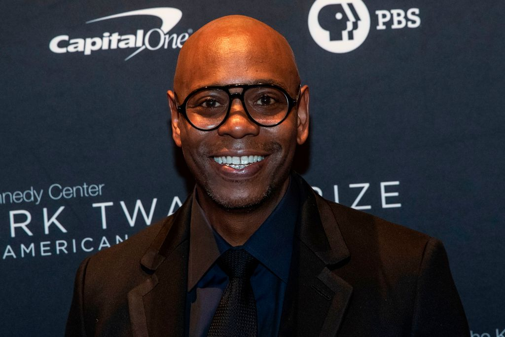 Dave Chapelle smiling in front of a repeating background