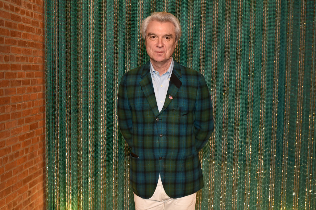 David Byrne smiling in front of a blue-green backdrop