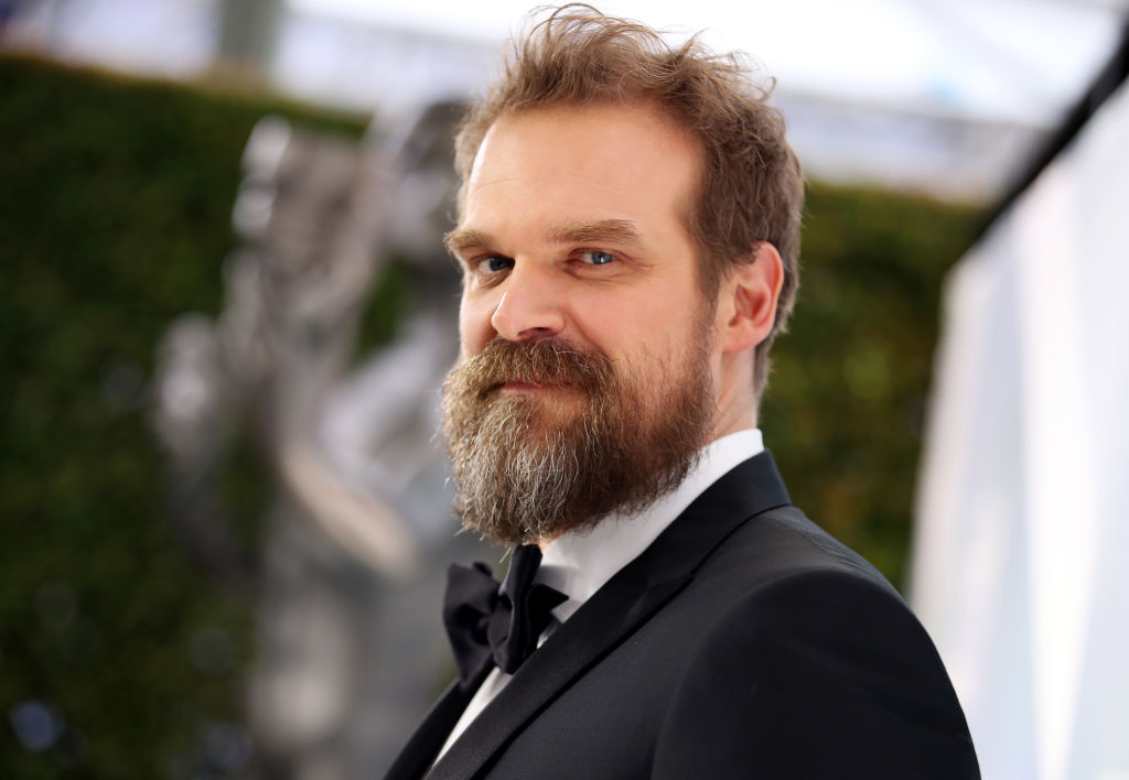 David Harbour looking at the camera to his side