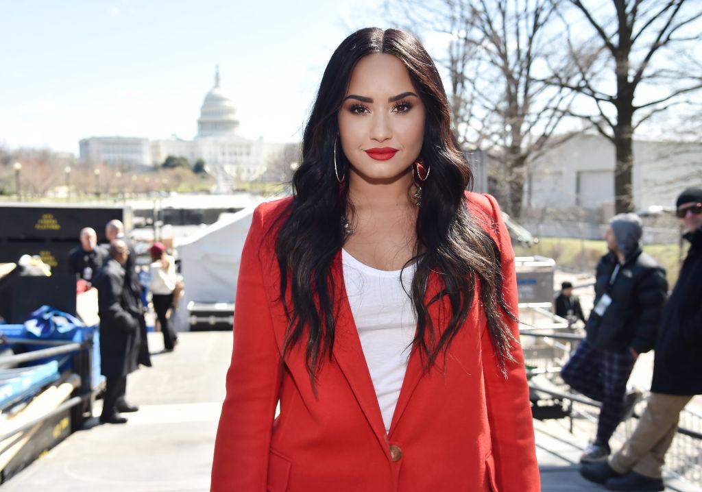 Demi Lovato smiling in a red blazer