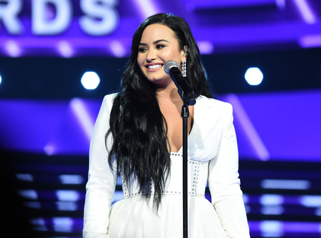 Demi Lovato smiling in a white dress, standing on a stage in front of a microphone