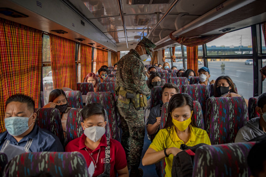 A Filipino policeman inspects a bus at a checkpoint as authorities begin implementing lockdown measures on March 16, 2020