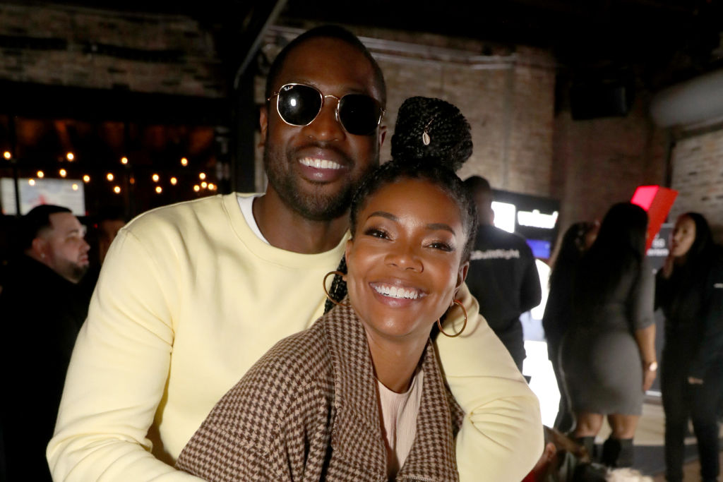 Gabrielle Union and Dwyane Wade embracing, smiling at the camera