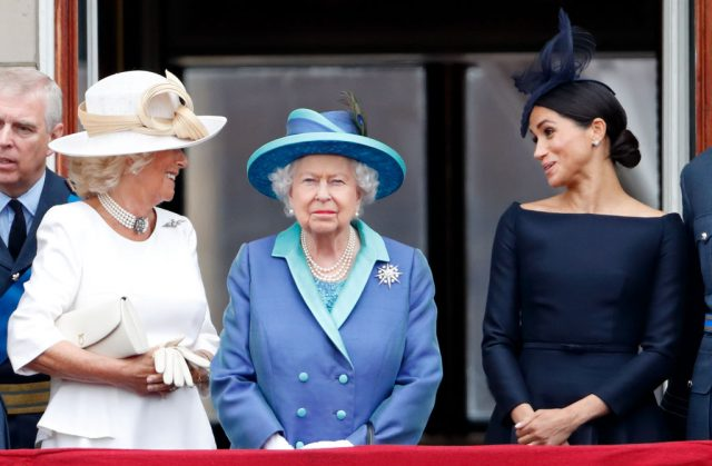 Camilla, Duchess of Cornwall and Meghan, Duchess of Sussex stand behind Queen Elizabeth II as they watch a flypast to mark the centenary of the Royal Air Force on July 10, 2018