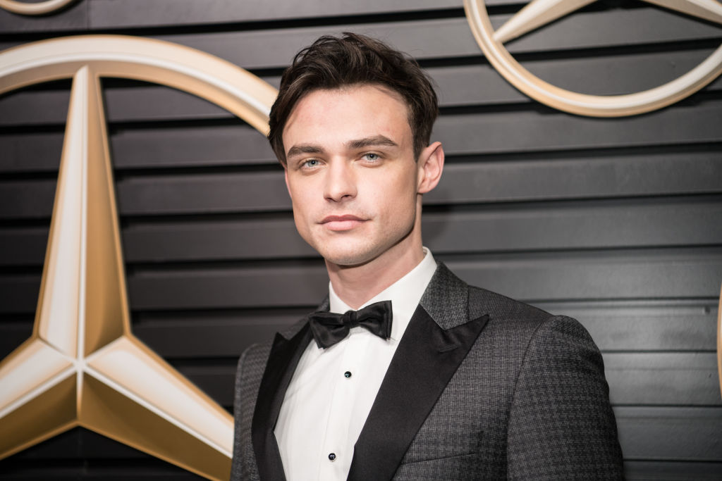 Thomas Doherty of the new 'Gossip Girl' cast in front of a repeating background in a tux