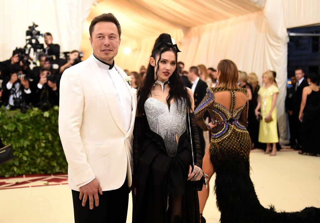 Elon Musk with his arm slightly around Grimes