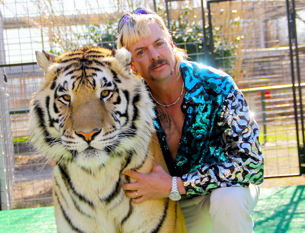 Joe Exotic in a sequined shirt hugging a tiger