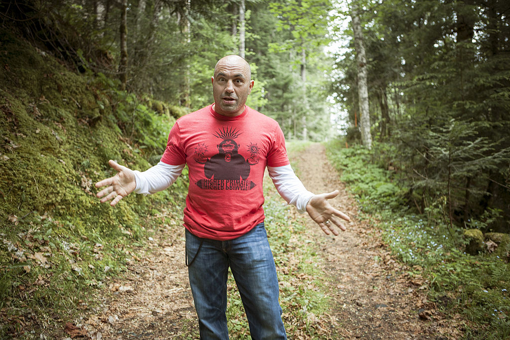 Joe Rogan in a red t-shirt on a wooded trail