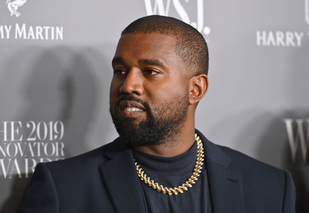 Kanye West looking off camera in front of a repeating background