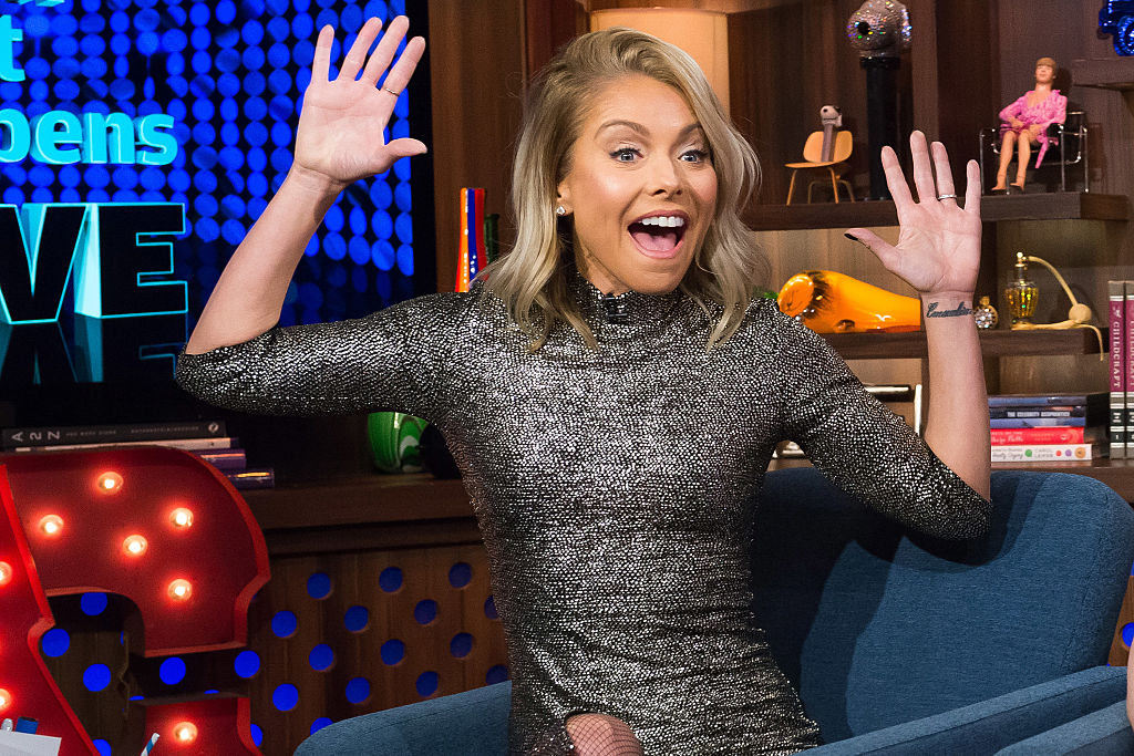 Kelly Ripa in a silver dress with her arms up and a look of shock