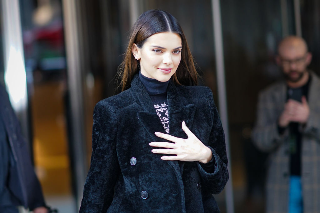 Kendall Jenner in a furry black coat smiling, look down away from the camera