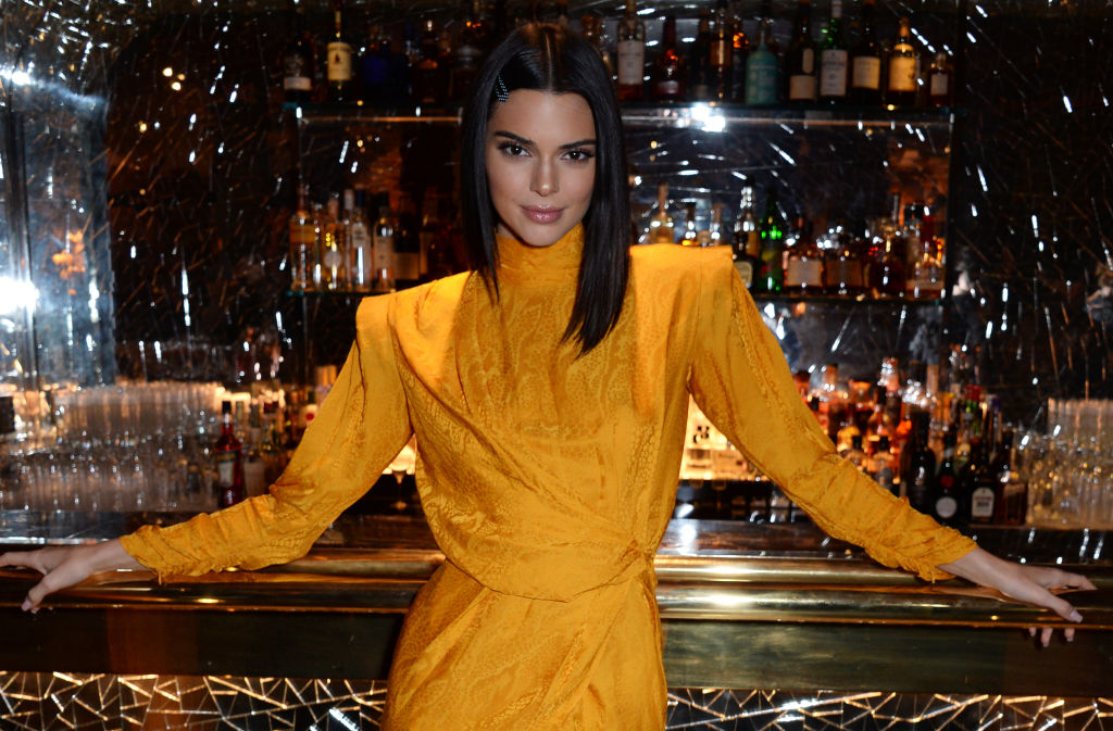 Kendall Jenner smiling with her arms resting outstretched on a bar