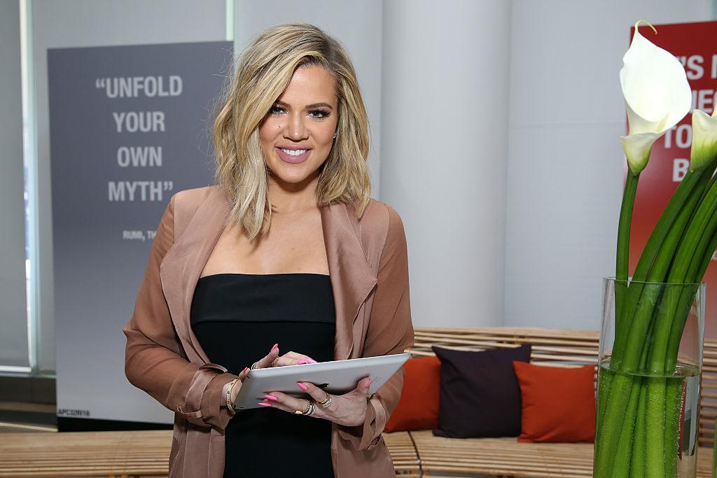 Khloé Kardashian smiling at the camera holding a tablet