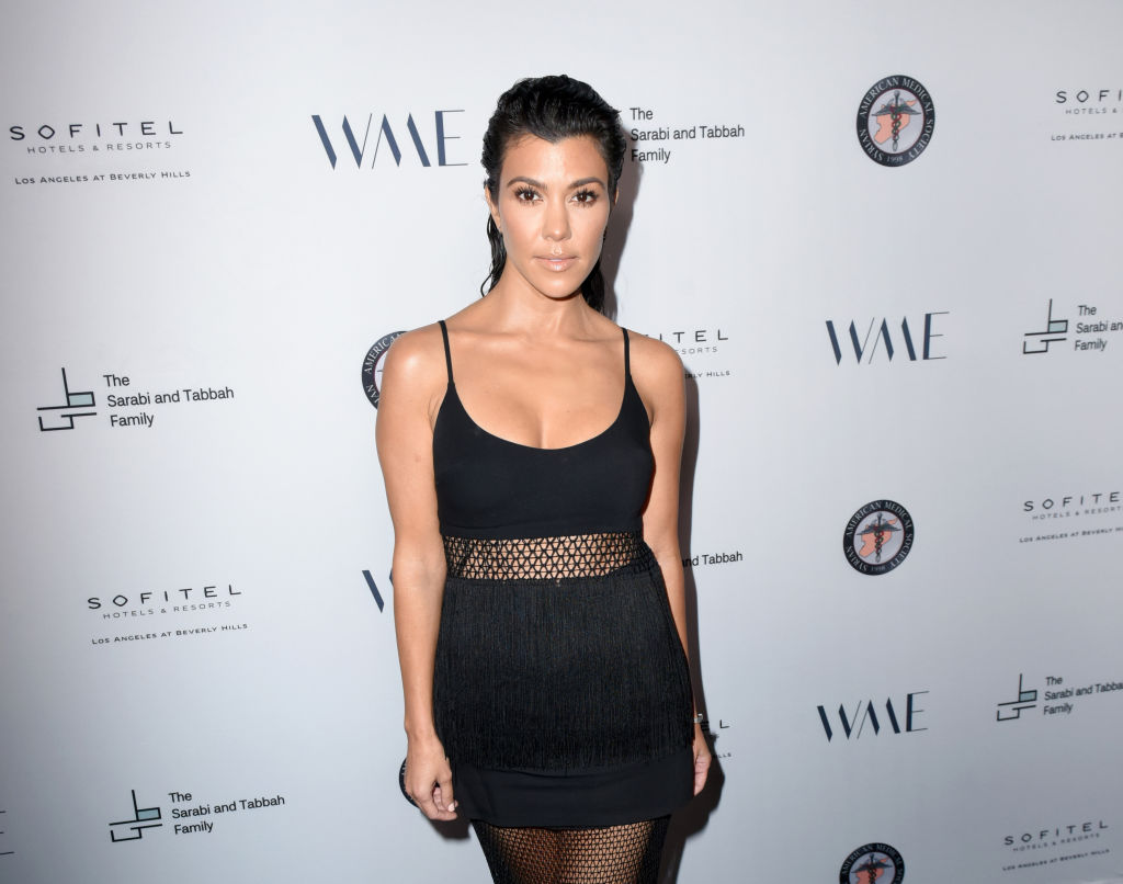 Kourtney Kardashian in a black mini dress in front of a repeating background