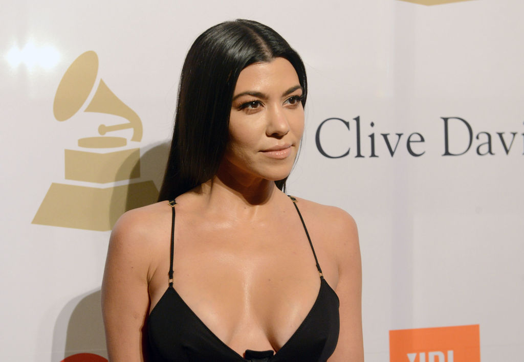 Kourtney Kardashian wearing a thin strapped black dress in front of a repeating backdrop