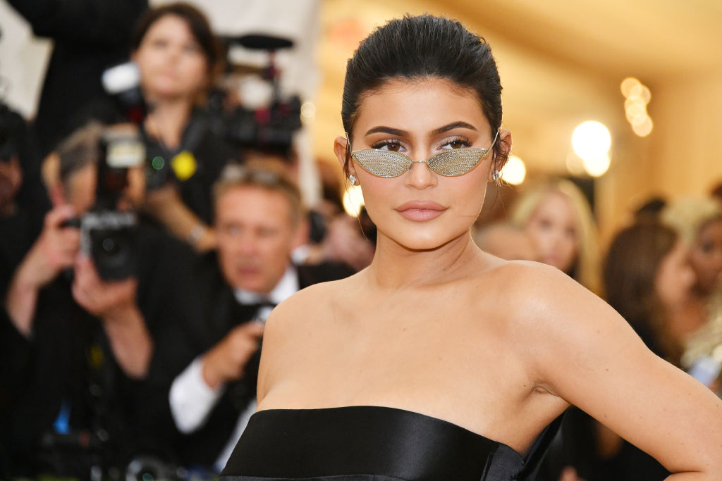 Kylie Jenner in sunglasses and a black dress looking off camera