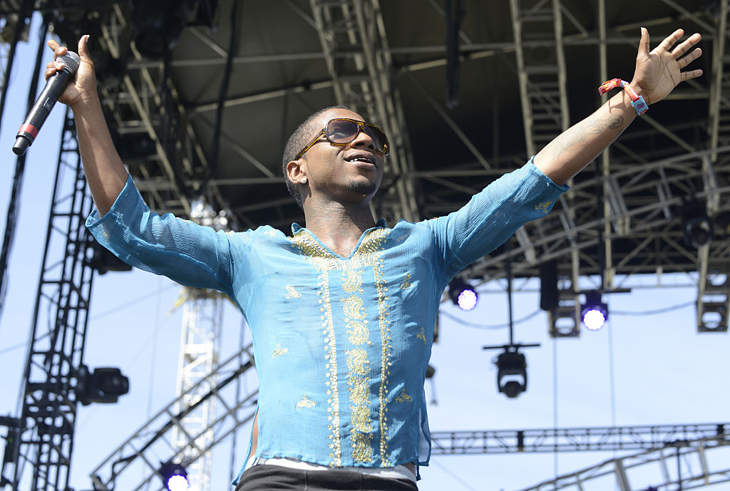Lil' B on stage with his arms outstretched