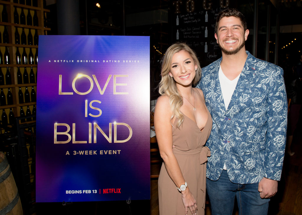 Amber Pike and Matt Barnett from 'Love is Blind' next to a promo sign