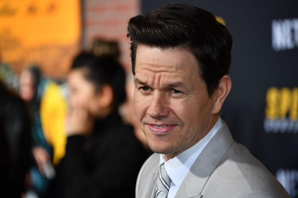 Mark Wahlberg in a white suit jacket looking away from the camera
