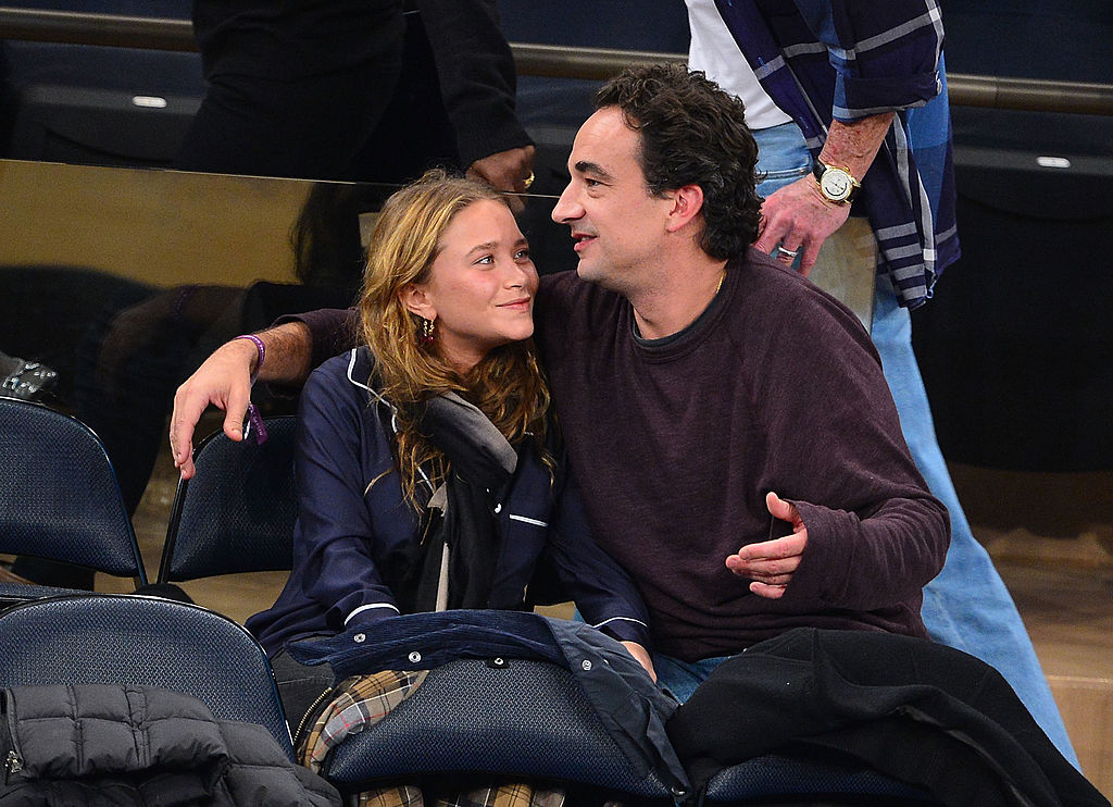 Mary-Kate Olsen smiling at Olivier Sarkozy in courtside seats