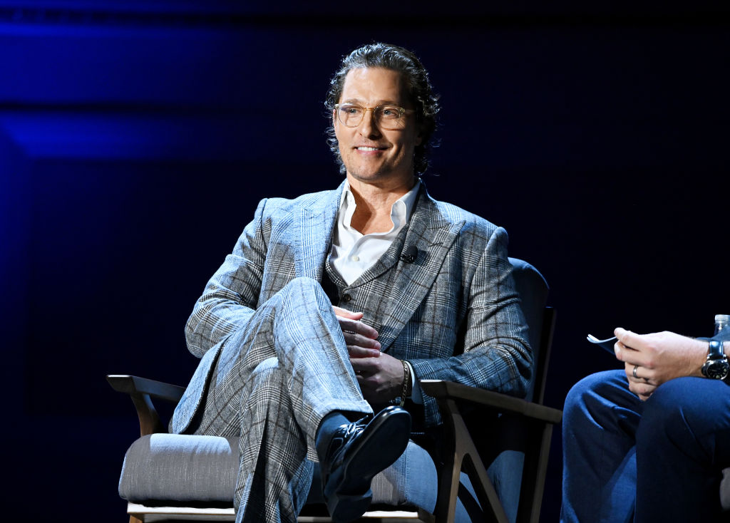 Matthew McConaughey in a plaid suit sitting on a stage