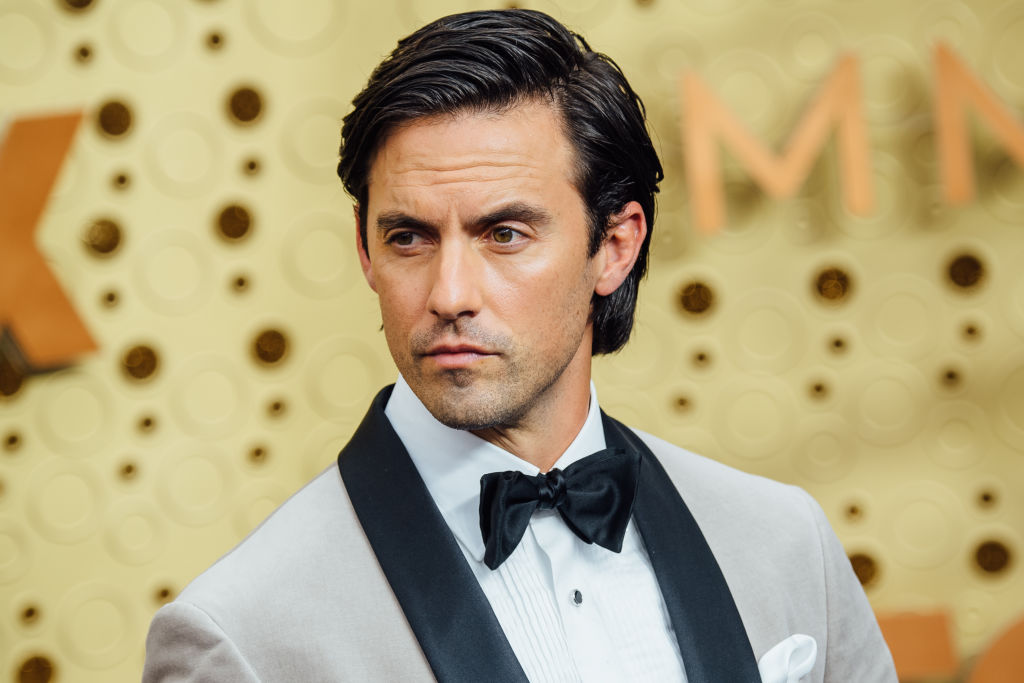 Milo Ventimiglia standing in front of a repeating background in a white and black jacket and black bowtie