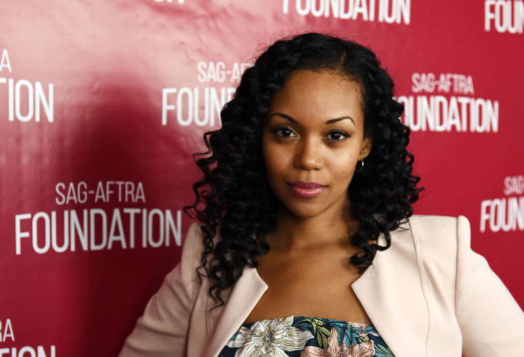 Mishael Morgan in front of a repeating background