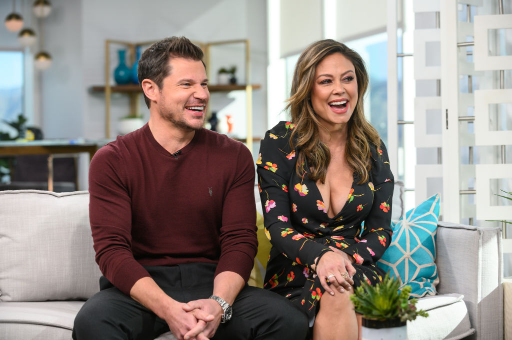 Nick and Vanessa Lachey sitting on a couch, laughing