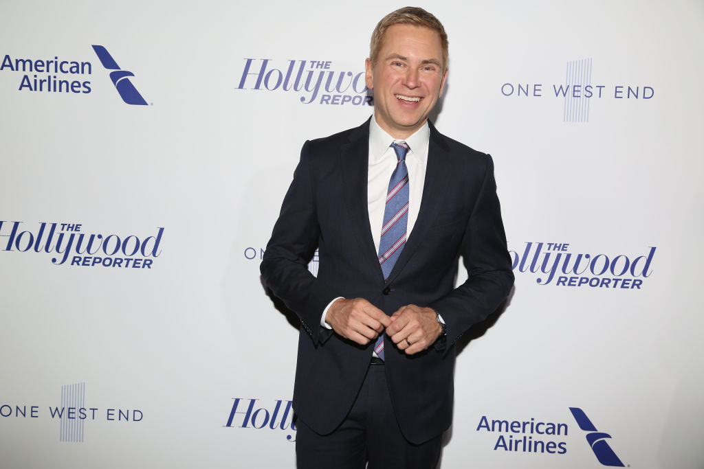 Pat Kiernan smiling in front of a repeating background