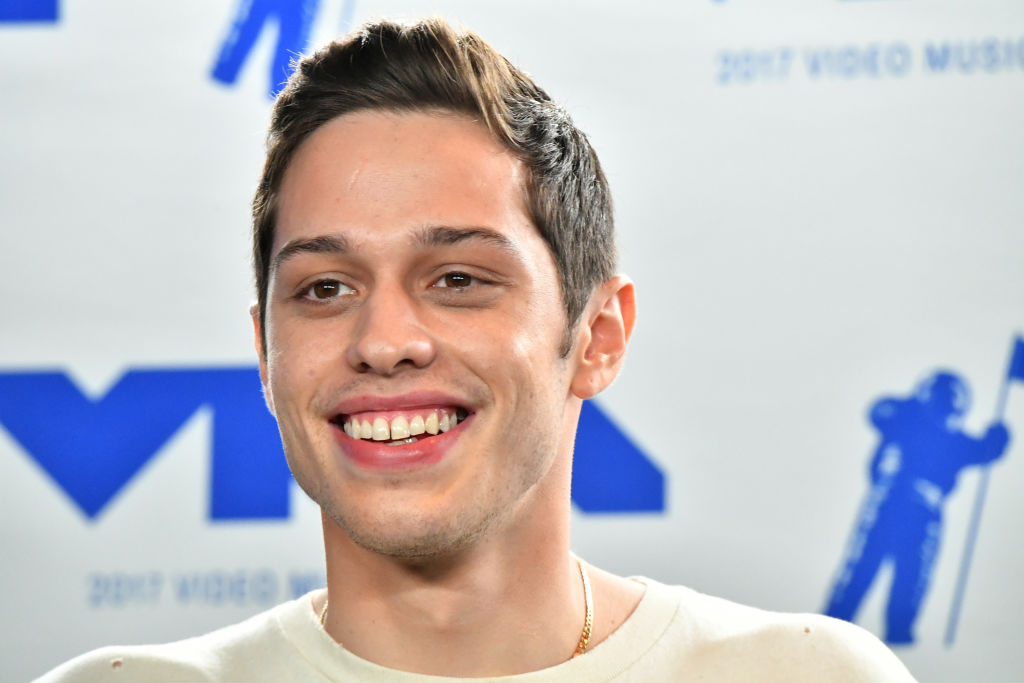 Pete Davidson smiling in front of a repeating background