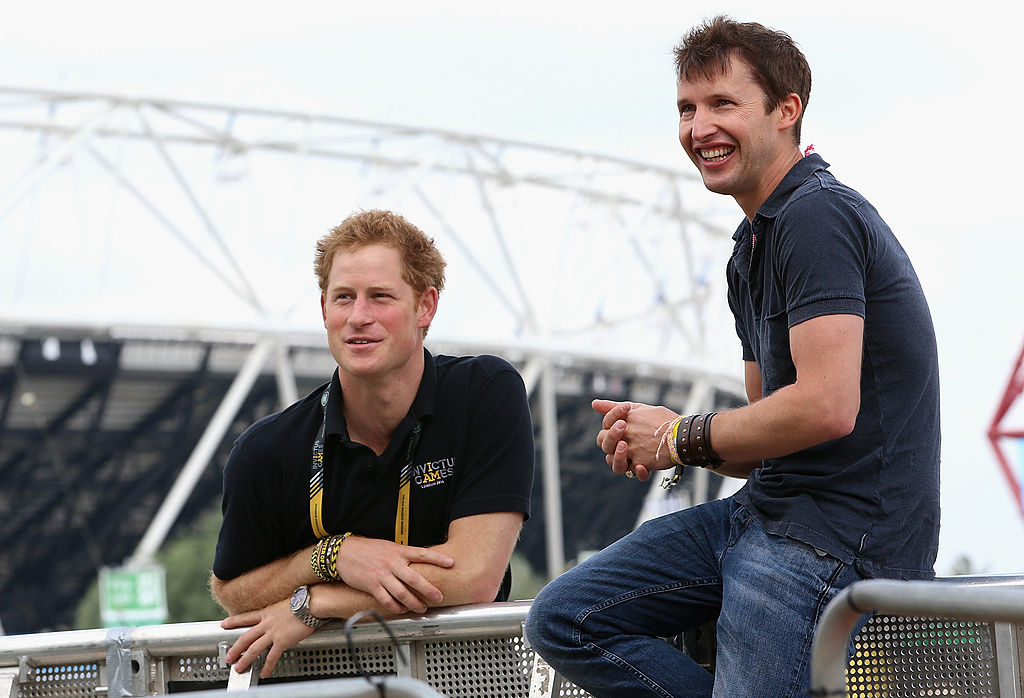 Prince Harry and James Blunt outside a stadium, smiling