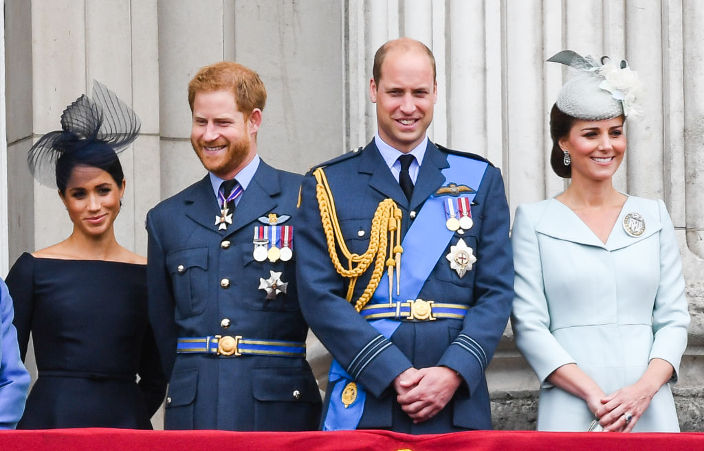 Meghan Markle, Prince Harry, Prince William, and Kate Middleton stand on the balcony of Buckingham Palace to view a flypast to mark the centenary of the Royal Air Force (RAF