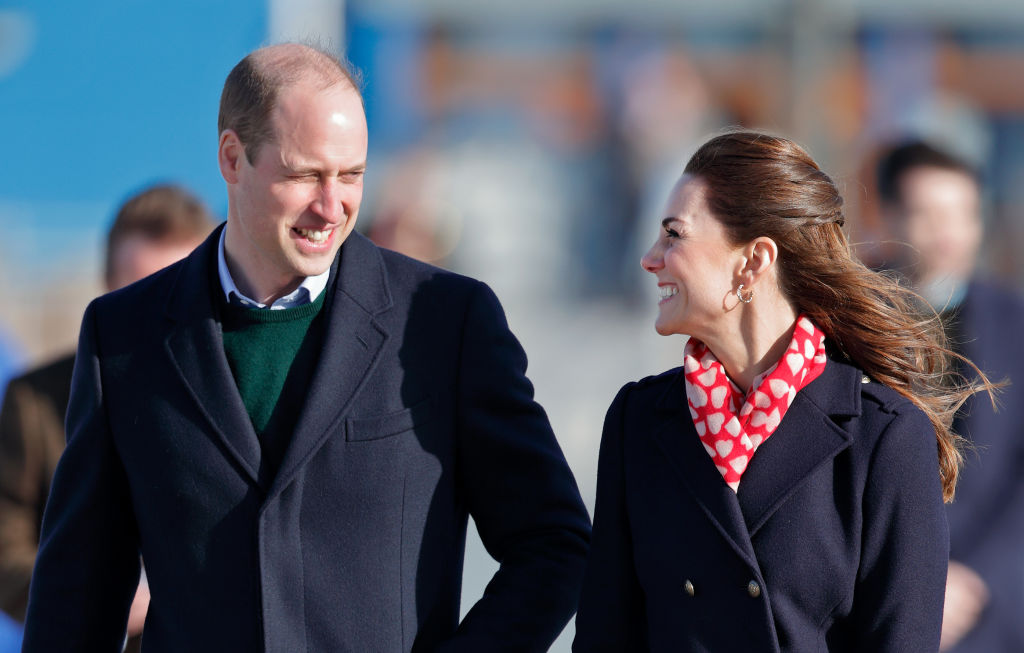 Prince William, slightly turned, smiling at Kate Middleton