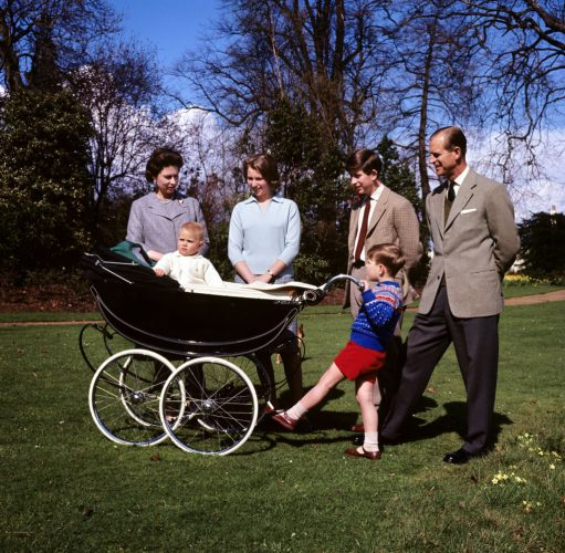 Prince Andrew pushes a baby Prince Edward in a stroller next to Queen Elizabeth II, Princess Anne, Prince Charles, and Prince Philip