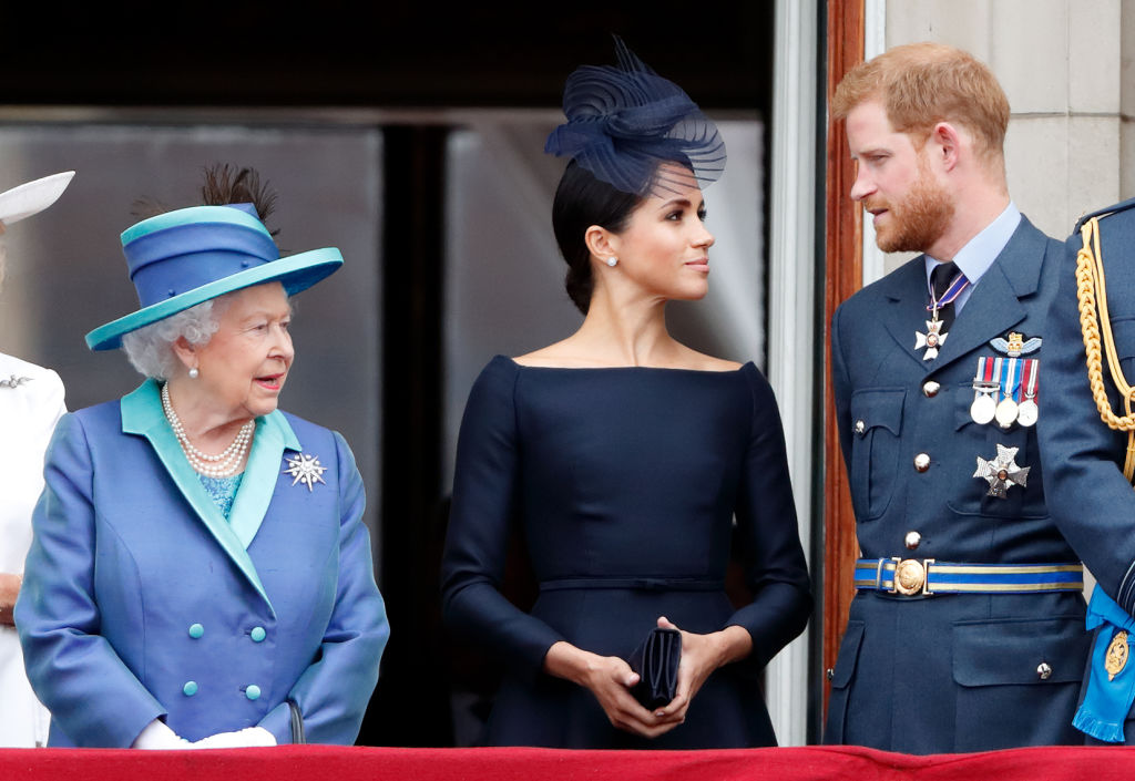 Queen Elizabeth, Meghan Duchess of Sussex, and Prince Harry watch a flypast to mark the centenary of the Royal Air Force from the balcony of Buckingham Palace