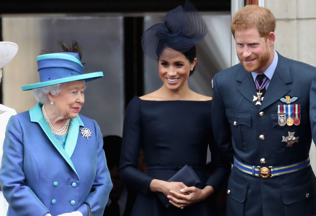 Queen Elizabeth II, Meghan Markle, and Prince Harry watch the RAF flypast on the balcony of Buckingham Palace