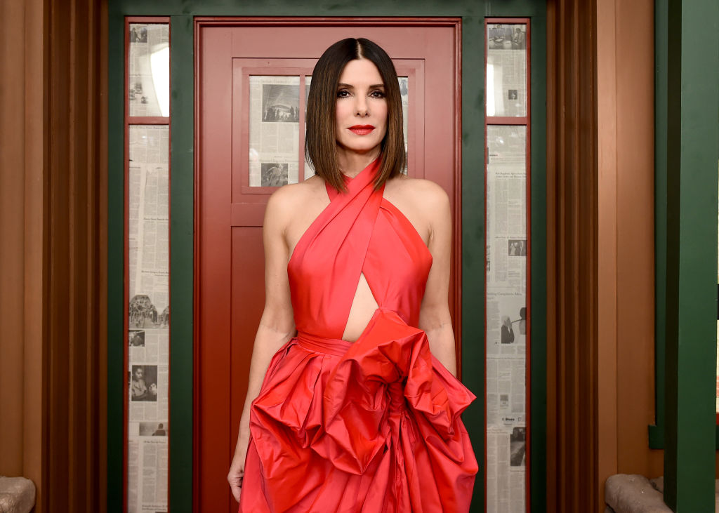 Sandra Bullock smiling in front of a door