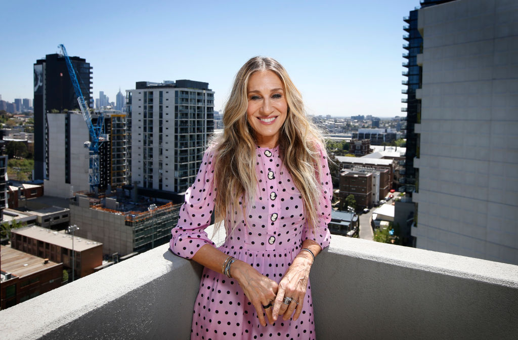 Sarah Jessica Parker in a pink dress on a balcony smiling
