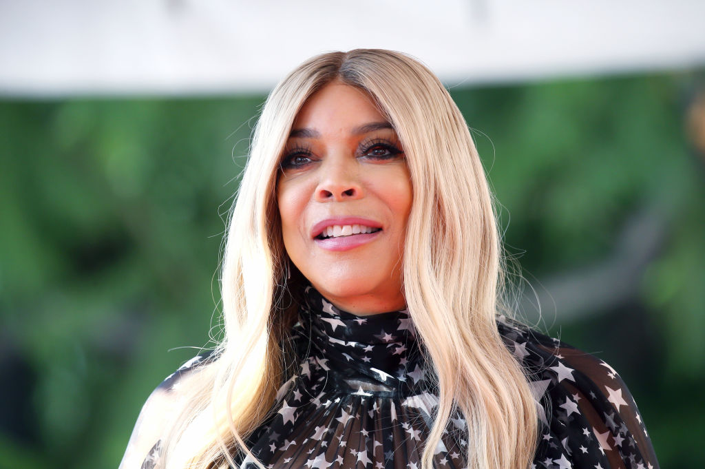Wendy Williams in a black mock neck shirt standing in front of greenery
