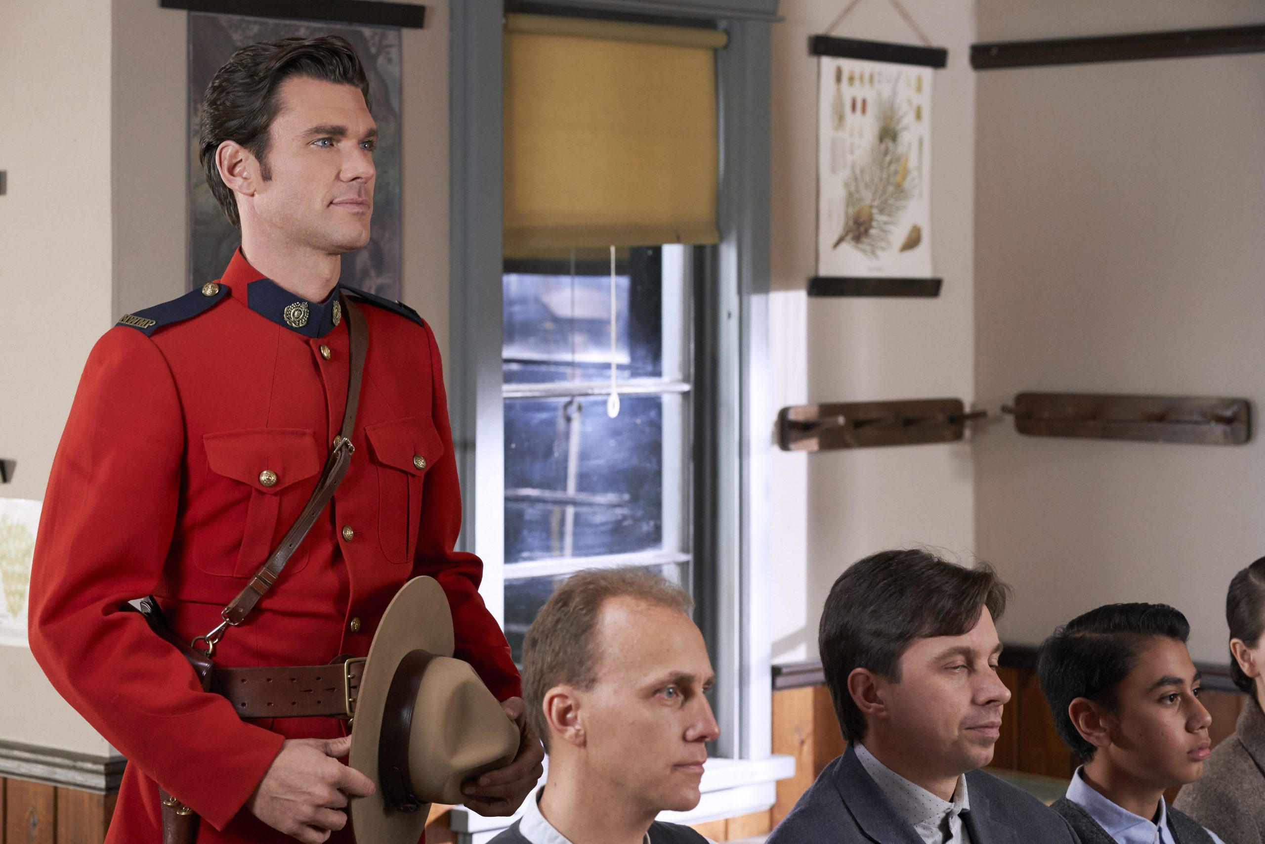 Kevin McGarry as Nathan, wearing red jacket and holding his hat, in 'When Calls the Heart'