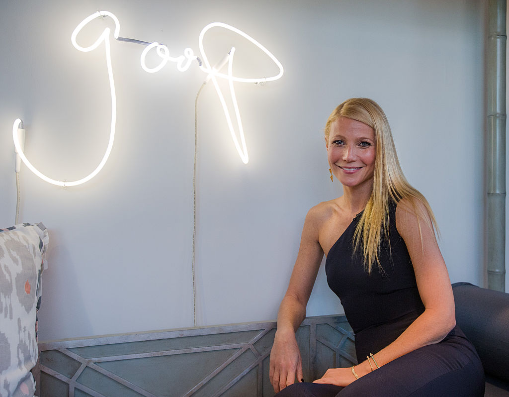 Gwyneth Paltrow posing in front of a goop sign