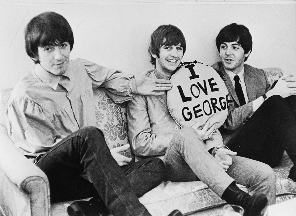 "George Harrison, Ringo Starr and Paul McCartney of The Beatles with an ""I Love George"" pillow"