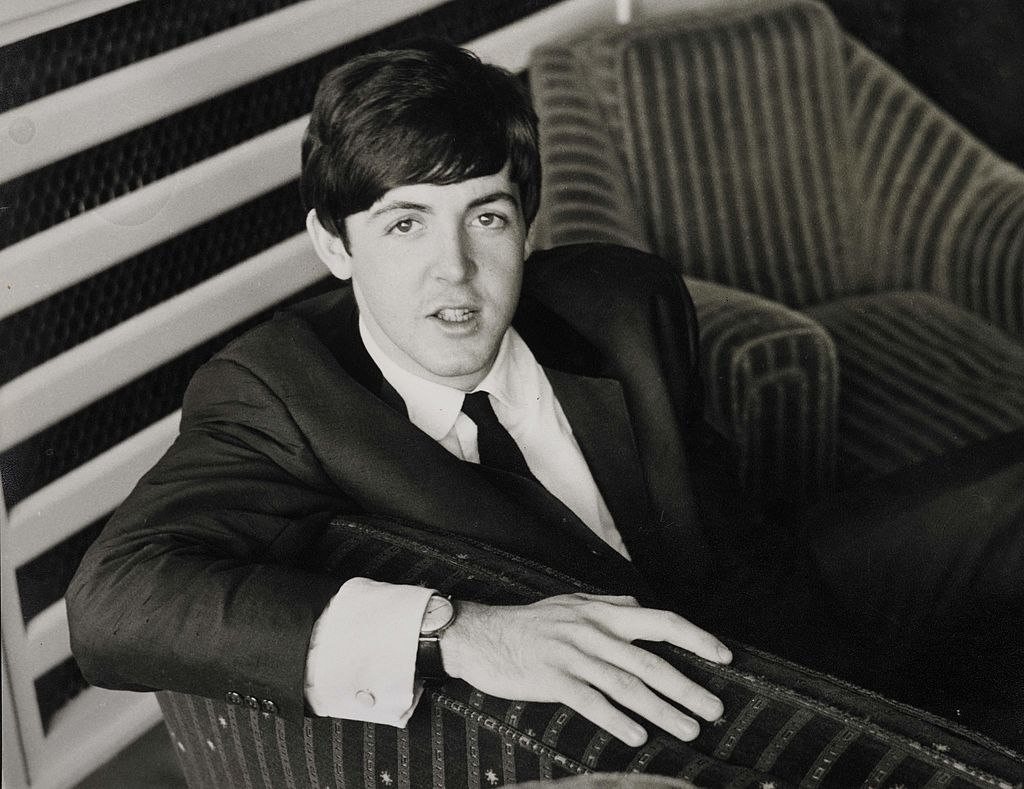 Paul McCartney sitting on a chair near a striped wall